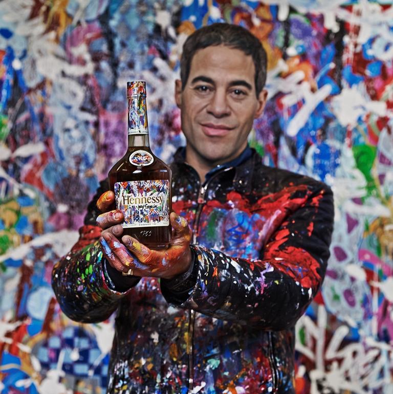 El artista grafitero Joone muestra su botella de Cognac Hennessy